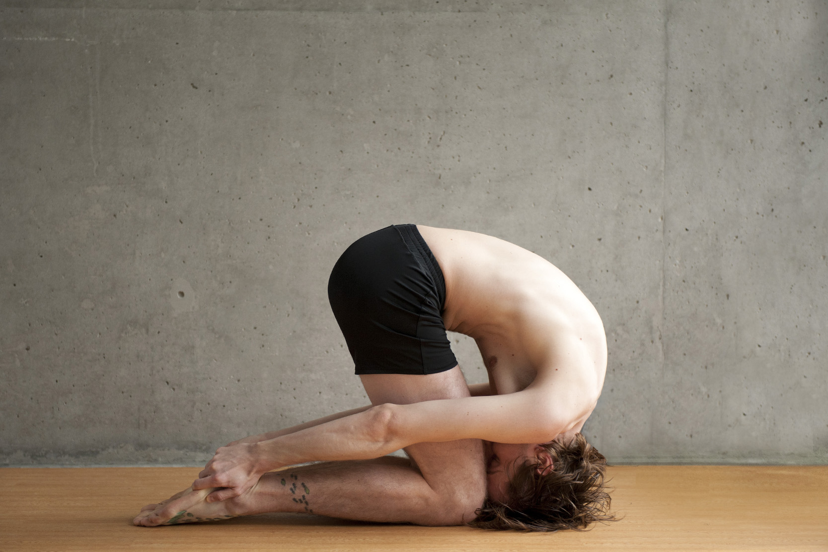 Man with tattoos Doing Rabbit Pose