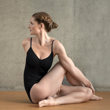 Woman doing spinal twisting pose Bikram Yoga Pose
